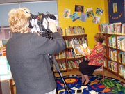 "As Lorraine Gluch, left, captures the scene on videotape, Vikki Jo Stewart, special projects coordinator for the Kansas State Library, reads ""No Matter What"" aloud at the Lansing Community Library. The book is the focus of the ""One Book, One State"" program aimed at newborns to 5-year-olds throughout Kansas. The reading can be seen on LGTV, Channel 2, at 7 p.m. Friday, 7 p.m. Saturday, 5 p.m. Sunday, 8:30 p.m. Monday and 9 p.m. Wednesday."