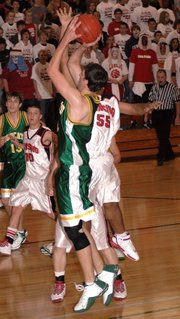 Lansing High junior Jeff Jackson swats Basehor forward Jacob Schierbaum's shot.