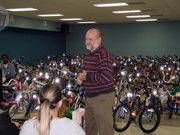 Lansing Correctional Facility Warden Dave McKune stands in front hundreds of bikes refurbished by prisoners and on their way to new homes.