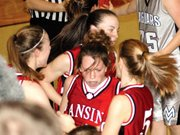 Katie Nietzke, center, is mobbed by Lansing High teammates Amanda Radovich, left, Nichole Twitchel, back, and Brittney Lang after being fouled while scoring on a layup during the second overtime Friday night. Nietzke scored a career-high 17 points during the victory.