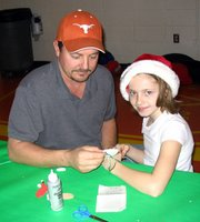 Charles Woods and his daughter, third-grader Kaitlyn Wood, make a Santa necklace.