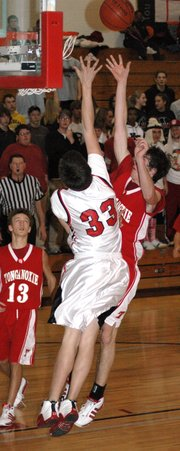 Austin Reynolds alters the shot of a Tonganoxie player during Lansing's 48-40 victory.