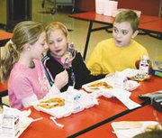 Starside Elementary School third-graders Monica Bererra, Kelsey Nelson and Greg Clarkson talk quietly at lunch. The students say the school's Silver Spoon award system encourages better manners at lunchtime.