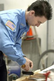 Officer Chris King uses a roller to transfer a dusted fingerprint from a porous surface to some lifting tape.