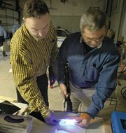Chief Terry Horner (left) and Officer Elmer Stewart use an ultra-violet flashlight to enhance detail on a fingerprint.