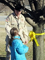 Staff Sgt. Charles Batorson and his daughter, Lansing Elementary School second-grader Savannah Batorson, get ready to cut down a yellow ribbon from a tree at the school. The school put up the ribbons for students' family members who are serving overseas in the military. Batorson recently returned from a second tour in Iraq.