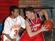 Lansing High senior point guard Cody Mohan, right, goes eye-to-eye with Atchison's Anthony Downing on Tuesday afternoon at the Tonganoxie Invitational Tournament.