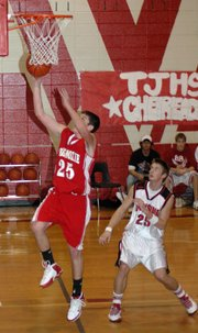 Tonganoxie sophomore Gabe Belobrajdic goes up for a layup as Lansing's Chris Wagner looks on.