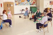 Alinda Sabin leads Madelyne Otto, Sue Allen, Judith Schafer, Delores Makepeace and Mary Manly in a series of chair exercises during a recent post-lunch visit to the De Soto Senior Center. Sabin visits the center twice a week as part of the Johnson County 50 Plus program.