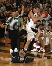 Lansing High senior Cody Mohan avoids stepping on a Mill Valley player after a blocking foul was called.