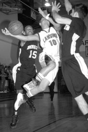 Lansing High senior Cody Mohan is fouled on his way to the basket.