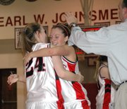 Lansing High's Amanda Radovich and Katie Nietzke celebrate their Class 5A substate first-round victory Thursday night as coach Keith Andrews gives Nietzke a congratulatory pat on the head.