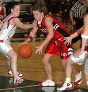 Lansing High sophomore point guard Katie Nietzke tries to split two Shawnee Heights defenders off the dribble in the first half.