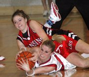 Lansing High sophomore forward Christine Cordes battles for a loose ball with a Shawnee Heights player Saturday night.
