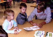 Kindergartners Delaney Kellum and Jarod Griggs practice reading with volunteer Jessica Monk, a Lansing High School senior. They are using guided reading books that are meant to help them learn words and recognize what a sentence looks like. Kindergarten teachers Andrea Rothmeyer and Vickie Kelly received a grant from the Lansing Educational Foundation Fund to purchase the books.