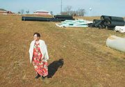 Anna Mary Landauer stands in a field she used to farm. In 2002, the long-time Basehor resident sold 31 acres to developers, with the agreement she can live in her house, pictured in the background, for as long as she wants to stay there. Basehor's new Casey's General Store, on property formerly owned by Landauer, is pictured to the left of Landauer's home.