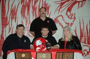 Logan Ryan, seated center, signed a letter-of-intent on Feb. 17 to play football at Highland Community College. Ryan, a Lansing High senior, was joined at the signing ceremony by his parents, Dennis and Sue Ryan, seated, and LHS coach Bill Pekarek, standing.