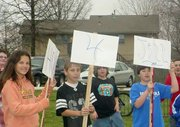 """Students in Barb Alonzi's fifth-grade class hold signs that read """"Honk"""" """"4"""" """"Jill"""" outside Lansing Intermediate School. Jill Carroll, the  American journalist kidnapped Jan. 7 in Iraq, is the niece of Alonzi. Carroll was freed Thursday, prompting the small celebration at the school."""