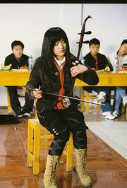 A student from Kaifeng No. 5 Middle School in China plays the erhu at a party for the Americans on March 25.
