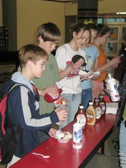 Students line up to pile toppings on their ice cream at the voting party for the William Allen White Children's Book Awards on Thursday, March 30, at Lansing Middle School. Students had to read five books nominated for the award to attend the party.