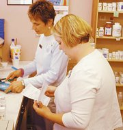 De Soto pharmacist Lori Murdock and her technician Laine Long have found themselves busier since the Medicare prescription drug plan became effective.