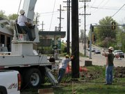 Workers with R/S Electric maneuver a 75-foot-tall utility pole into the ground near Main and Ida streets. The new electric pole will hold lines for Westar. Utilities are being relocated along Main Street to make way for the Main Street System Enhancement Project.