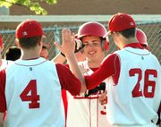 Lansing High junior Matt McMillin is congratulated by his teammates after hitting a two-run home run against Atchison.
