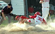 In a cloud of dust, Lansing High sophomore Kris Hernandez slides safely into home against Atchison.