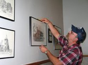 Myron Olson, the county's maintenance supervisor, levels a picture of the Kickapoo Land Office. The picture is one of about 50 on display in an ongoing exhibit at the Leavenworth County Courthouse.
