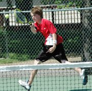 Lansing High freshman Ezra Carpenter smashes a return during the third-place match at No. 2 doubles on Thursday at the Leavenworth Invitational.
