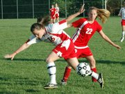 Lansing High sophomore midfielder Erin Griffen loses her footing during a collision with Ottawa's Lauren Reed.