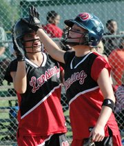 Lansing High sophomores Morgan Chiles, left, and Amanda Darrow celebrate after they scored the go-ahead runs in the seventh inning of Lansing's 4-2 victory against Tonganoxie.