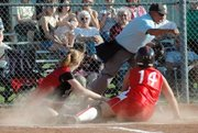 Lansing High pitcher Brittney Lang tags out Tonganoxie's Ronnie Grizzle in the seventh inning of Lansing's 4-2 victory. Grizzle tried to score after Lang threw a wild pitch.