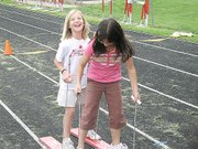 Jordan Maestas, left, and Tara Dupras, Lansing Intermediate School fourth-graders, try out one of the events at Field Day on Friday, May 5, at Frank Graham Field.