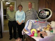"Leavenworth chiropractor Joe Jones, left, his assistant Elaine Rounds and Staff Sgt. Stuart Ford show some of the toys collected for ""Operation Iraqi Children."" Rounds, the mother of two soldiers in Iraq, got the idea for the drive from a support group of service members' wives, mothers, girlfriends and other relatives."