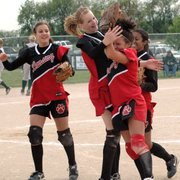 Lansing High's Morgan Chiles, Brittney Lang, Kasey Denney and Nicole Holland celebrate after Denney turned an unassisted double play that sealed Lansing's 2-1 victory and gave the Lions a share of the Kaw Valley League championship.