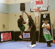 "NBA legend Daryl Dawkins, who referred to himself as ""Chocolate Thunder"" during his playing days, blocks a dunk attempt during a dunk contest at Fort Leavenworth's Harney Gymnasium. Dawkins was a judge at Friday's contest, part of an NBA-themed day at the fort."