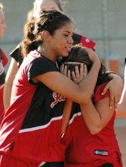 Lansing High sophomore Jasmine Holland comforts senior Kasey Denney after Lansing's 1-0 loss to St. Thomas Aquinas at the Class 5A softball state tournament.