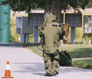 Sgt. William Slusher of the Leavenworth Bomb Squad, wearing a protective suit, approaches a mailbox at Wiley's Wild Woods Mobile Home Park, 921 S. Main St. Slusher was going to place a detonation device in the mailbox, where a suspected bomb was discovered June 21.