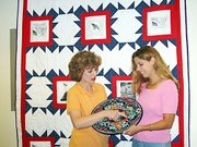 Council on Aging staffers Patty Willmeth, left, and Julie Angello admire a painted Mexican plate that will be sold at a silent auction July 7 to benefit the county's Meals on Wheels program. The plate was donated by Leavenworth business Abierto Puerto. They are standing in front of a flag quilt, also donated for the auction by Lansing resident Lula Dillon.