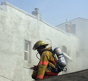Firefighters work from the roof of the building to combat the flames spreading within 726 Shawnee St., Leavenworth.