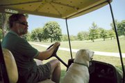 Michael Boaz, superintendent of Leavenworth Country Club, shown with his dog, Bubba, looks over a fairway at the club. Boaz is in charge of keeping the fairways, rough and greens at the club in tip-top shape - not an easy job in the Kansas summer.