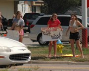 Freshman volleyball players try to attract business to their car wash at Petro Deli. Lansing High School volleyball players conducted car washes on Saturday, Aug. 12, at three area locations as a fundraiser for the teams.