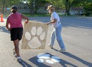 "Rachel Elkins and Kay Walden carry a stencil during the Lansing Lions Booster Club's ""Paint the Paws"" event. Volunteers painted paws on the streets around Lansing High."