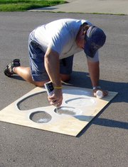 Rich Hauver uses a wooden stencil to paint a paw on Sunday near Lansing High School.