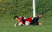 Lansing High senior goalkeeper Alex Burton makes a diving save during the first half Thursday against Mill Valley.