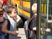Lansing elementary school students board their buses after school last week. More than 1,000 students are taking advantage of free additional busing in the Lansing school district this year.