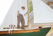 Bill Davis stands aboard the sailboat he has built in the backyard of his Baldwin City home. Although the boat still hasn't seen water yet, Davis has big plans for what will become a dream come true.