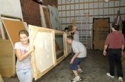Lansing High School drama club students move props out of the club's storage shed last month. The shed is being relocated to make a parking lot once construction commences on the new high school auditorium.