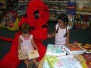 Isabel Mesa, left, and her sister, Guilia, visit with Clifford the Big Red Dog. The girls were attending the Lansing Community Library's Scholastic Book Fair on Saturday. The library met its goal of $1,500 for the fair, which ran Aug. 29-Sept. 2.